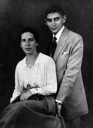 Portrait en noir et blanc. Deux personnes occupent l'essentiel de la photo : une jeune femme à gauche, assise, et un jeune homme debout à sa droite, proche d'elle. Il s'agit de l'auteur Franz Kafka et sa fiancée Felice Bauer. Elle porte une blouse blanche, une longue jupe, des bijoux, et un sac sur ses genoux ; il porte un costume clair simple. Ils ont l'air sérieux, mais souriant.