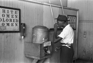 """Ségrégation racial-""""Negro drinking at """"Colored"""" water cooler in streetcar terminal, Oklahoma City, Oklahoma"""", Photograph by Russell Lee, July, 1939."""