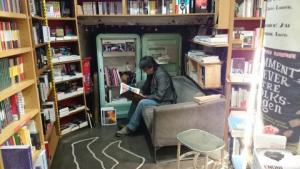 Coin lecture dans une librairie avec l'empreinte d'un corps à la craie sur le sol.