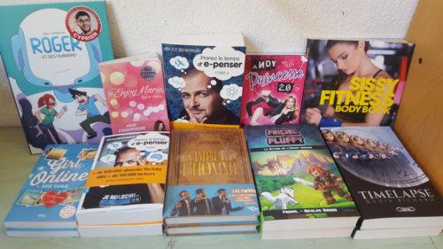 Différents livres de youtubeurs posés sur une table