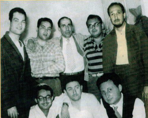 """Avocats d'Alger assignés en """"camps d'hébergement"""" à Berrouaghia (1957). En haut , de gauche à droite: Amokrane Amara, Amar Bentoumi, Kaddour Sator, Louis Grange et Mahmoud Zertal. En bas, de gauche à droite: Ghaouti Benmelha, Abdelhamid Hammad et Elie Guedj. Selon Ghaouti Benmelha, la photographie a été prise au lycée de Ben-Aknoun où lui et ses collègues avaient été ramenés de leurs camps respectifs en vue d'être présentés à un juge d'instruction (entretien du 28 octobre 2016)."""