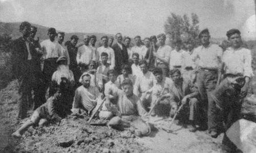 Fig. 8 : équipe de corvée sur le chantier d'une construction en terre à Oropos (Attique) en 1948. L'homme placé le plus à gauche tient par les pattes le coq qui a été sacrifié pour garantir une longue vie à la nouvelle bâtisse. On distingue un moule en bois rectangulaire dans le tas de terre au premier plan (tiré de Gkikakis 2007, 385).