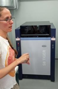 Fig. 6 : Noémie Müller, chimiste du Fitch Laboratory, devant le spectromètre (WD-XRF) Bruker S8 Tiger.