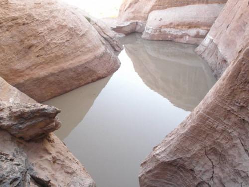Figure 1 : Le réservoir partiellement empli à la mi-décembre 2010, après un épisode de pluies abondantes. La marque sombre sur les parois gréseuses indique que la crue avait entièrement rempli le réservoir et débordé par dessus l'ouvrage. © anonyme, déc. 2010.