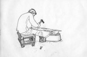 Fig. 2 : La petite enclume, qui sert de point de réaction à la frappe du marteau, enfoncée dans le plot en bois, est cachée par le genou et le mollet de l'artisan. Dessin de Moheb Chanesaz Nader d'après une photographie d'Ella Dardaillon au Souk al-Nahhasin de Damas (2007).