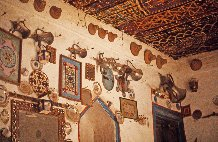 Intérieur de la pièce principale d'une habitation, appelée ṣuffa. Plafond peint et profusion de la décoration mobilière à forte charge symbolique,Sharqiyya d'Oman.
