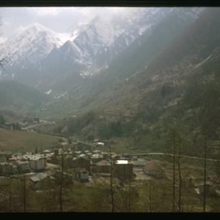 Val Germanasca : Vue sur Ghigo di Prali au fond d'une vallée avec montagnes enneigées en arrière plan dans le Val Germanasca (Piémont, Italie)