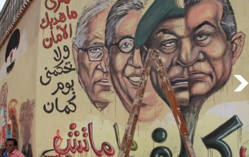 """Le graffiti (celui qui délègue reste au pouvoir, litt. """"ne meurt pas"""") entend dénoncer le caractère superficiel de la transition politique, l'auteur considérant que le pouvoir est seulement délégué par Moubarak à ses """"mandataires"""" successifs. Au fil de ses mises à jour, il met successivement en scène, dans ce rôle, le Maréchal Tantawi (2011) puis deux des candidats à sa succession, Amr Moussa et Ahmed Chafiq, puis enfin Mohamed Badie, le guide suprême des Frères musulmans (2012)."""