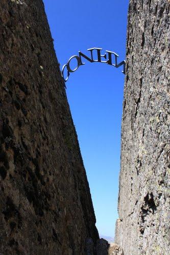 """""""La palabra abre la roca"""",leyenda de letras de hierro (48 cm) formando un arco sobre una grieta de 6 m en la cima oeste del Cerro Gallinero. La leyenda, ACONFINZ, se podría traducir como desde el comienzo al final todo está pensado, todo sucede con un fin"""
