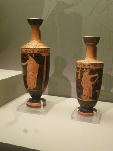 Lecitos áticos fig.rojas. c.460 aC. Hombre con bastón y columna dórica; mujer hilando. Museo Arte Cicládico (Atenas)