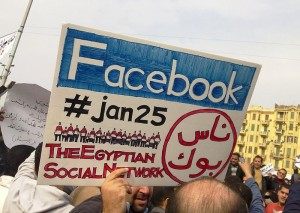 """Man holding a poster reading """"Facebook, #jan25, The Egyptian Social Network"""" during the 2011 protests illustrating the vital role played by social networks in initiating the uprising. Image by Essam Sharaf (CC-BY-SA 3.0)."""